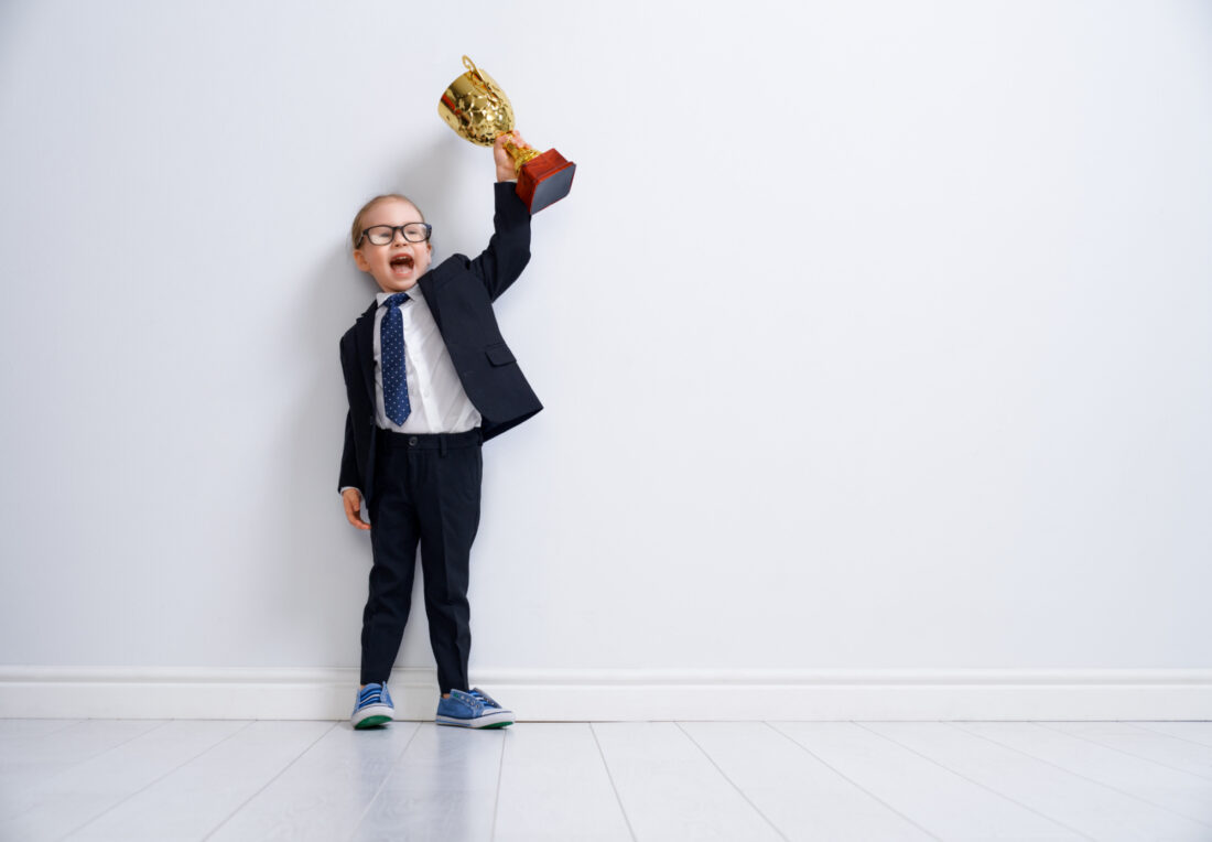 Child in suit lifting trophy