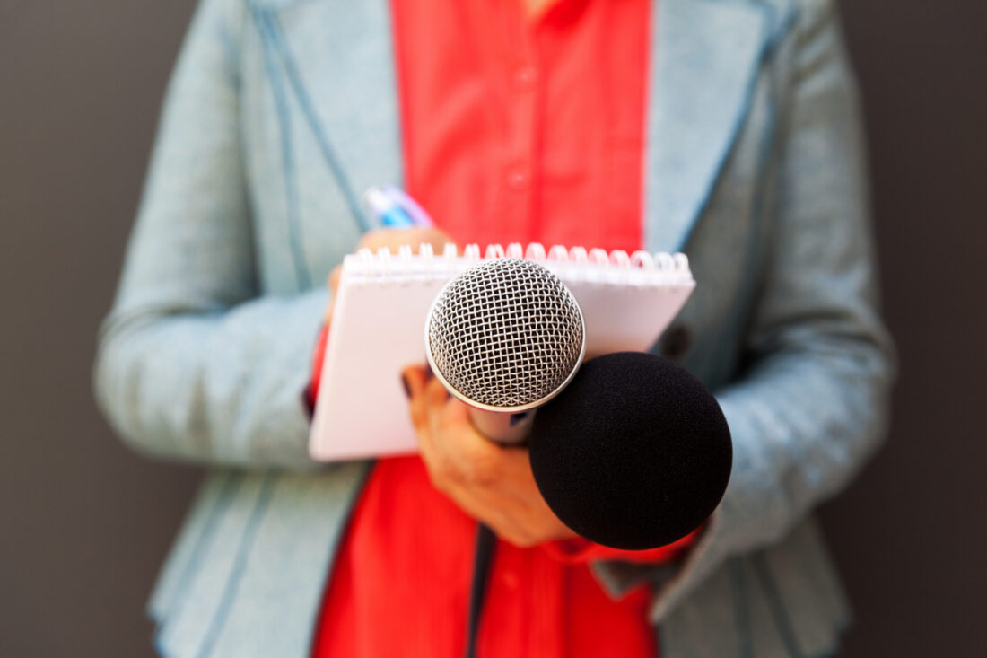 Female reporter at news conference, writing notes, holding microphone