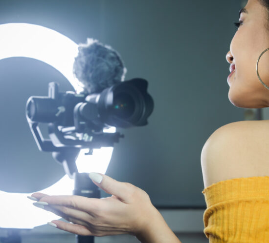 Influencer speaking to camera, lit by a ring light